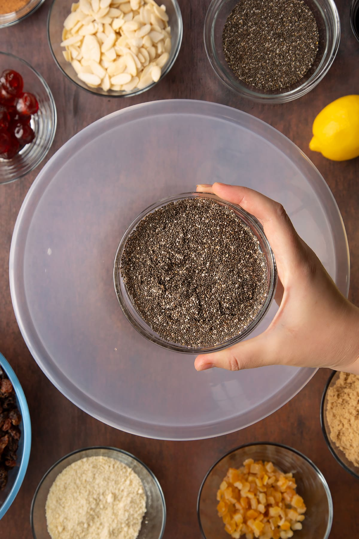 Hand holding a small bowl with chia seeds and water. Beneath is a larger bowl, surrounded by ingredients to make vegan Christmas cake.
