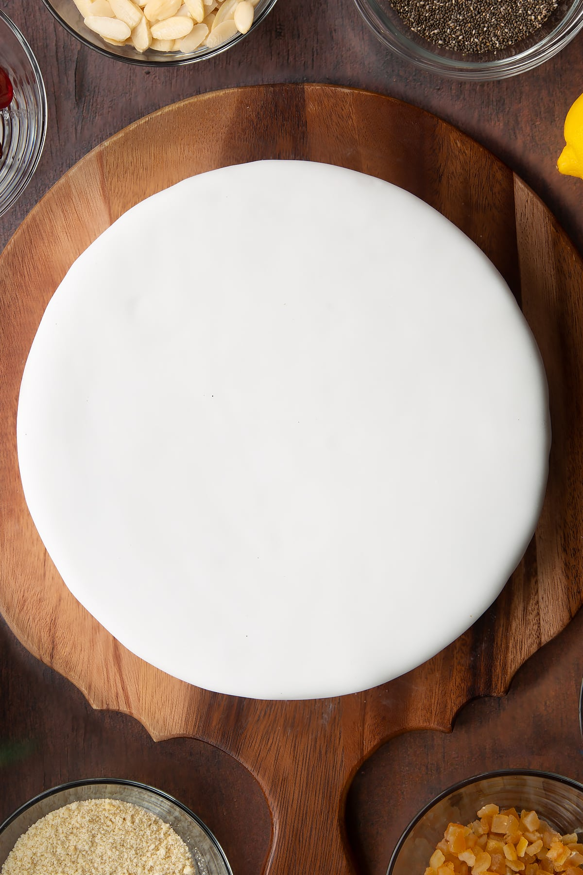 Vegan Christmas cake, topped with a disc of marzipan and covered with white sugar paste on a wooden board.
