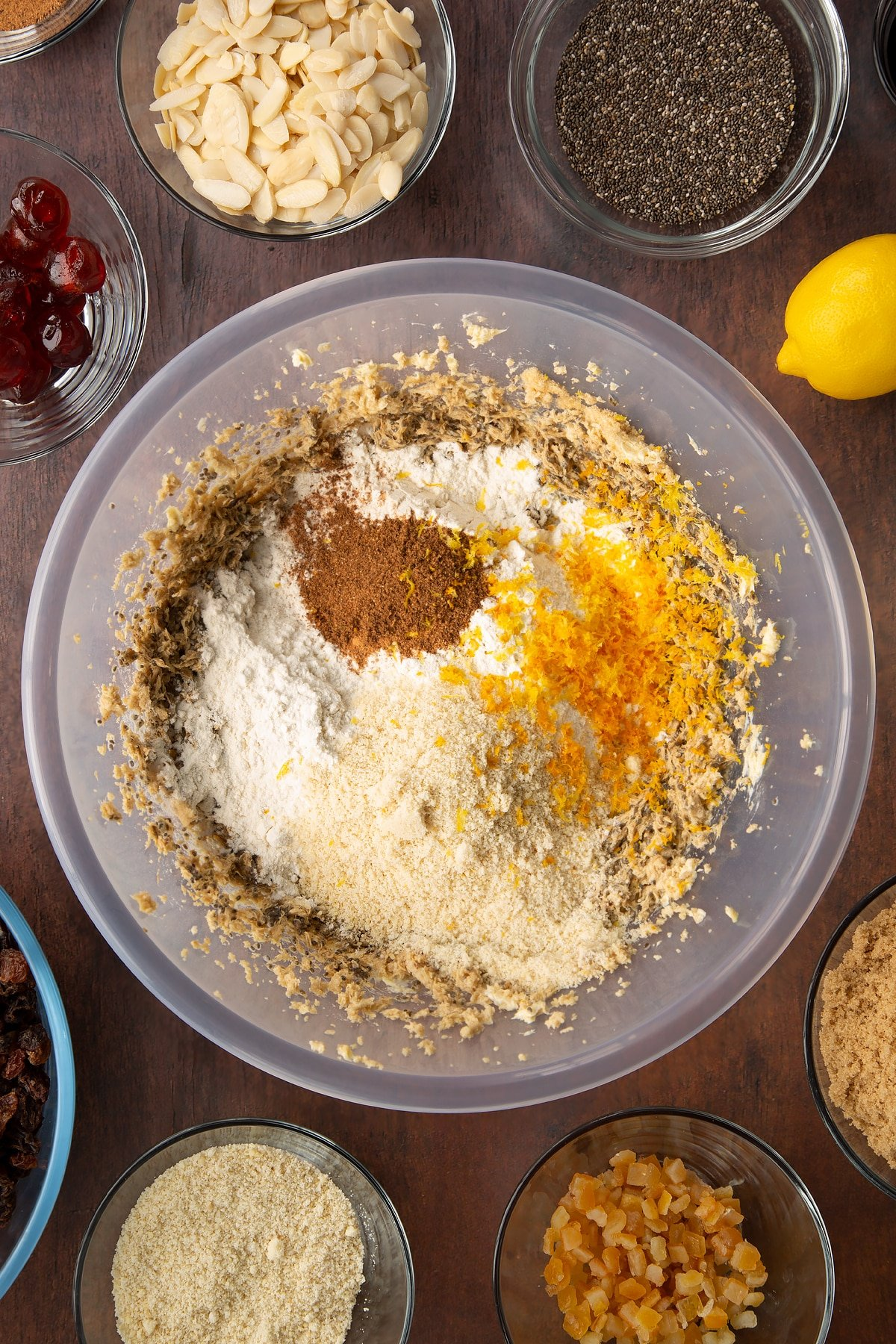"""Vegan butter, brown sugar, chia """"egg"""" and black treacle, whisked together in a large plastic bowl with Add the flour, ground almonds, mixed spice, nutmeg, orange zest and lemon zest on top. Ingredients to make vegan Christmas cake surround the bowl."""