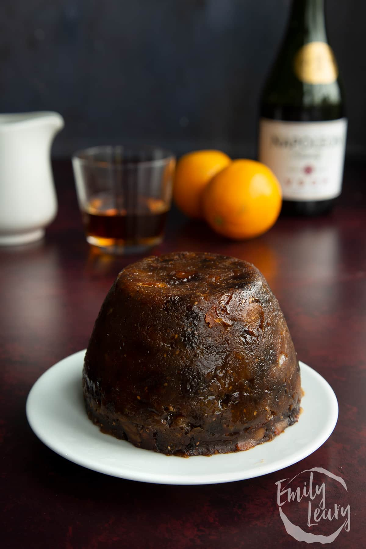 Steamed vegan Christmas pudding on a small white plate.