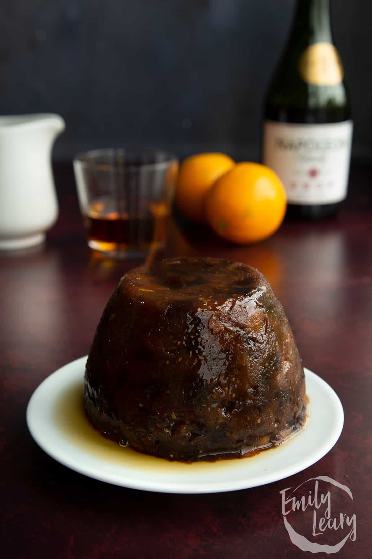Steamed vegan Christmas pudding on a small white plate. It has lit whisky on it.