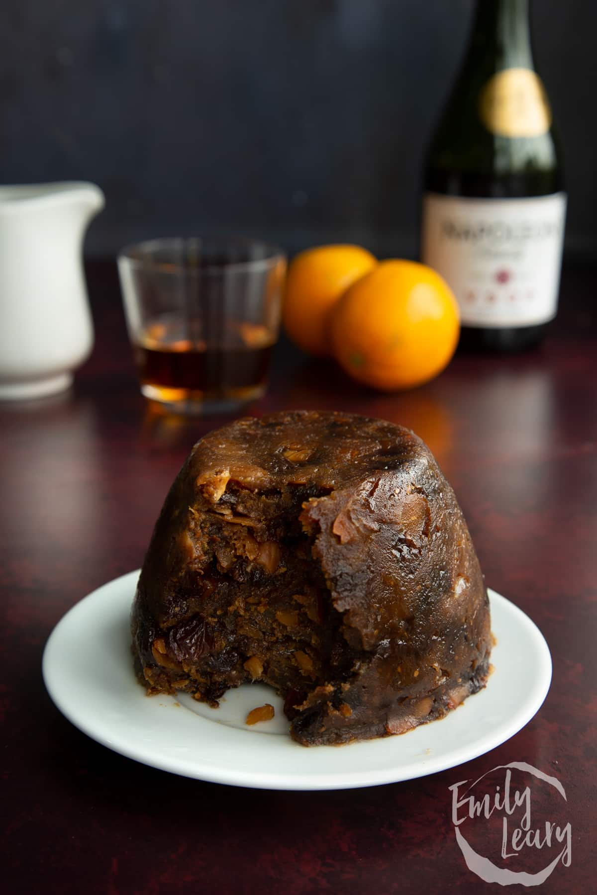Steamed vegan Christmas pudding on a small white plate. Part has been spooned away.