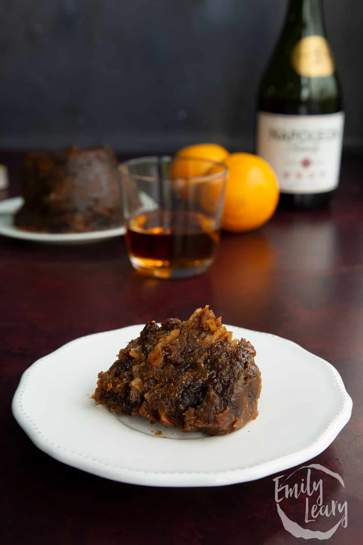 A piece of vegan Christmas pudding on a small white plate.