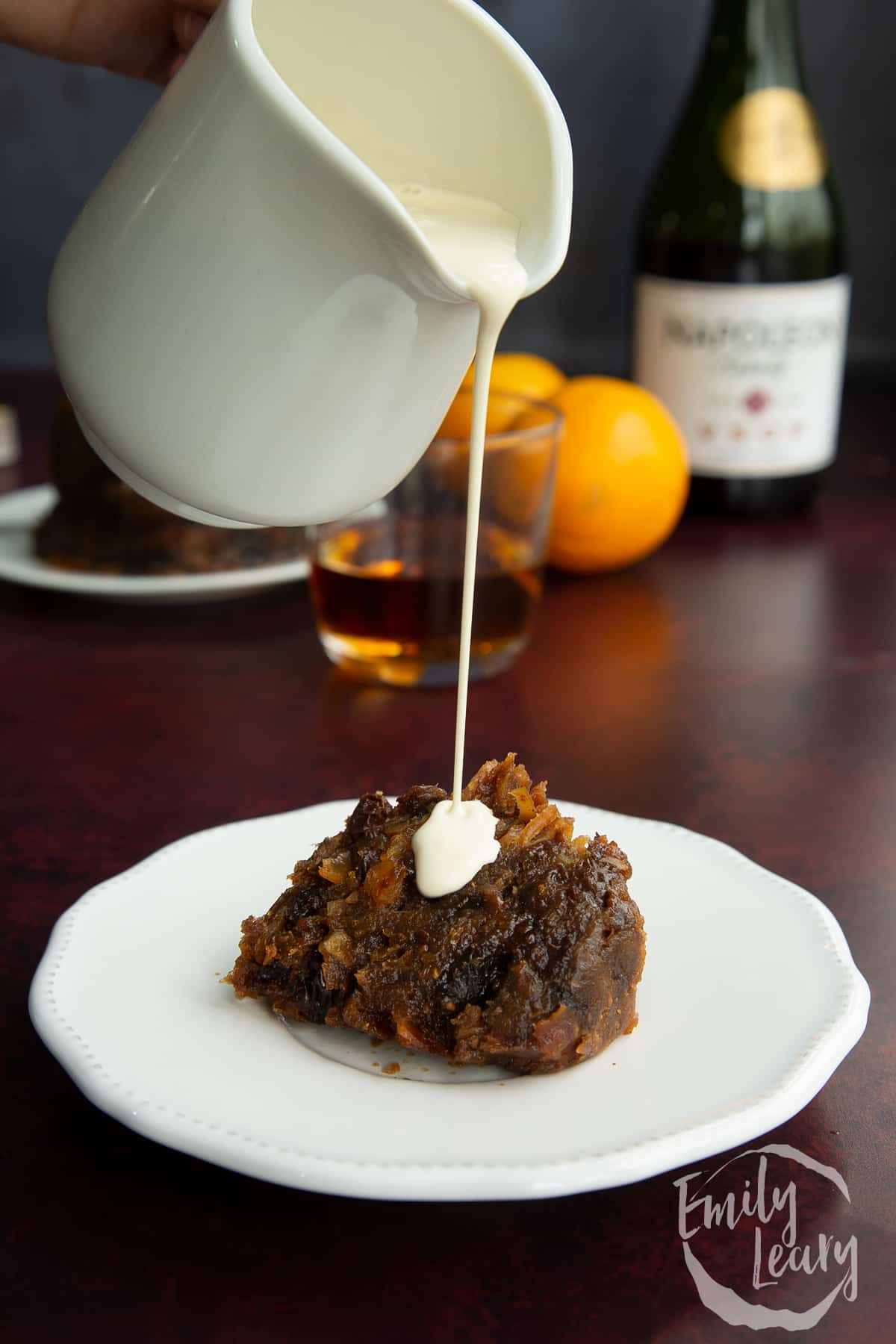 A piece of vegan Christmas pudding on a small white plate. Vegan cream is being poured on to it.