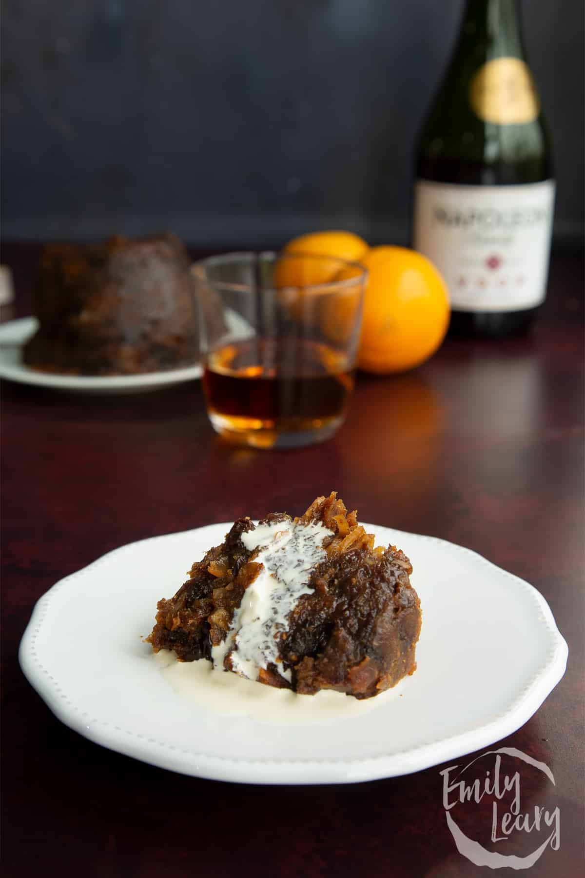 A piece of vegan Christmas pudding on a small white plate with vegan cream.