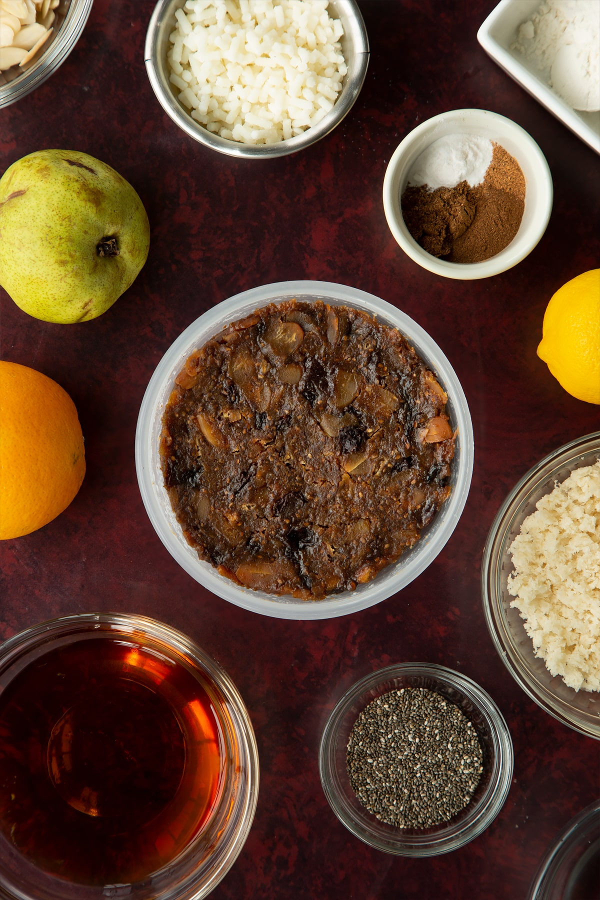 Steamed vegan Christmas pudding in a pudding basin. Ingredients to make vegan Christmas pudding surround the basin.