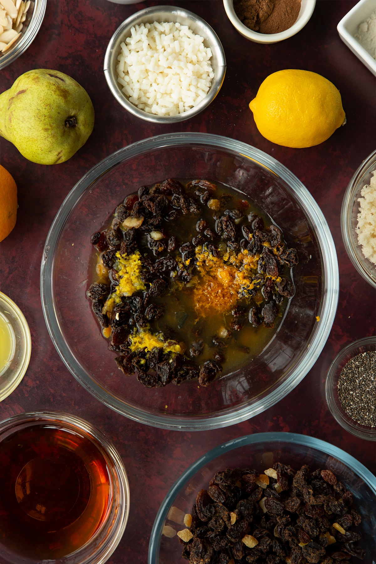 Mixed fruit, brandy, citrus juice and zest in a glass mixing bowl. Ingredients to make vegan Christmas pudding surround the bowl.