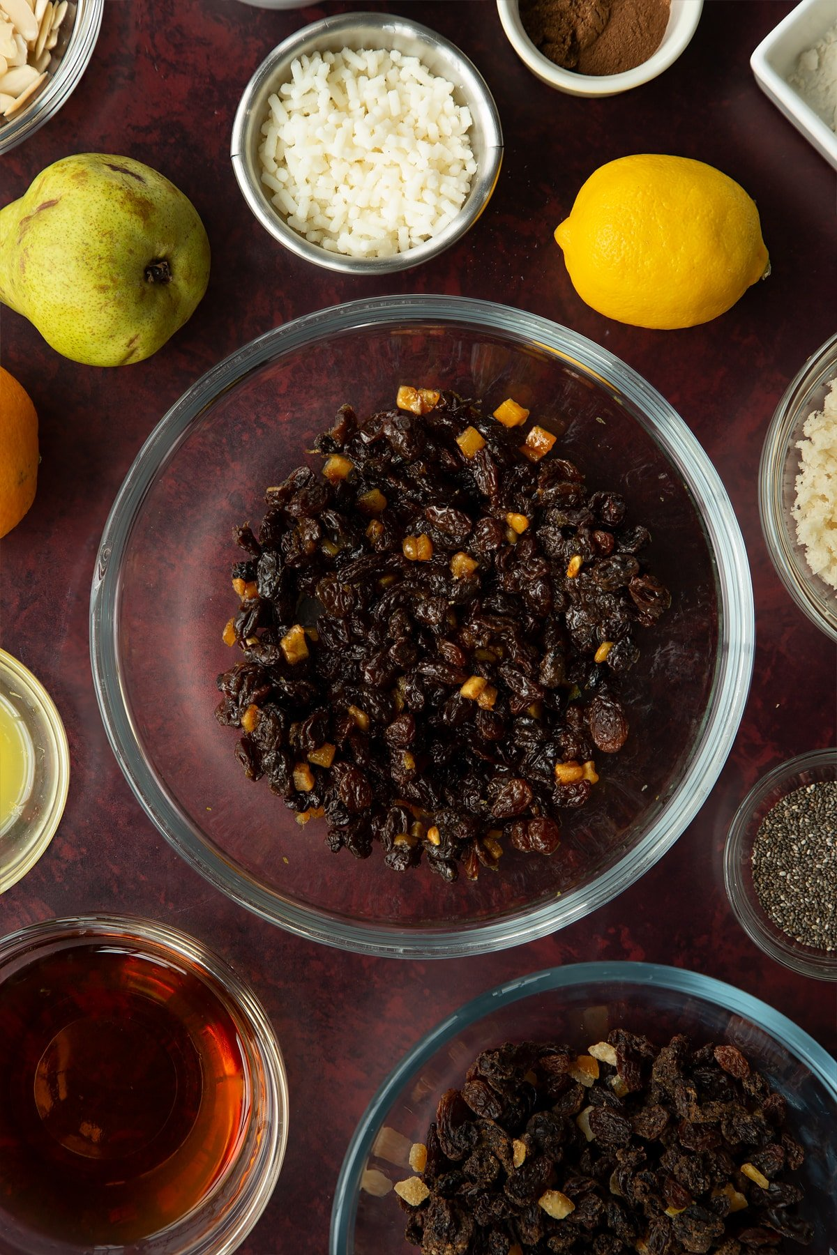 Mixed fruit cooked in brandy, citrus juice and zest in a glass mixing bowl. Ingredients to make vegan Christmas pudding surround the bowl.