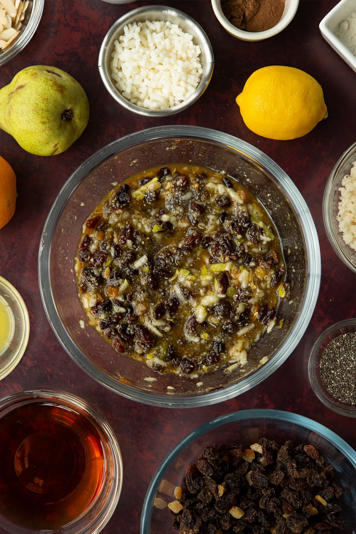 Plump mixed fruit, pear, soaked chia seeds, black treacle and sugar mixed together in a glass bowl. Ingredients to make vegan Christmas pudding surround the bowl.