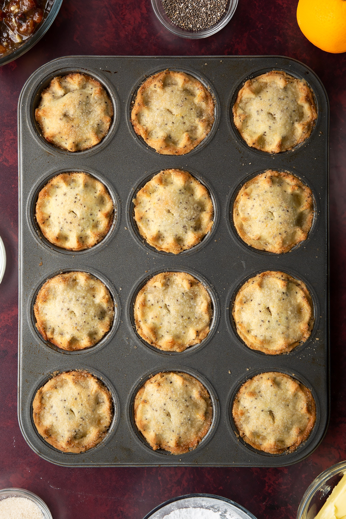 Freshly baked vegan mince pies in a muffin tray.