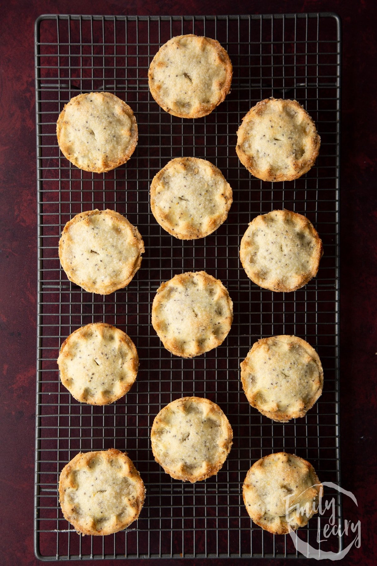 Freshly baked vegan mince pies on a wire cooling rack.