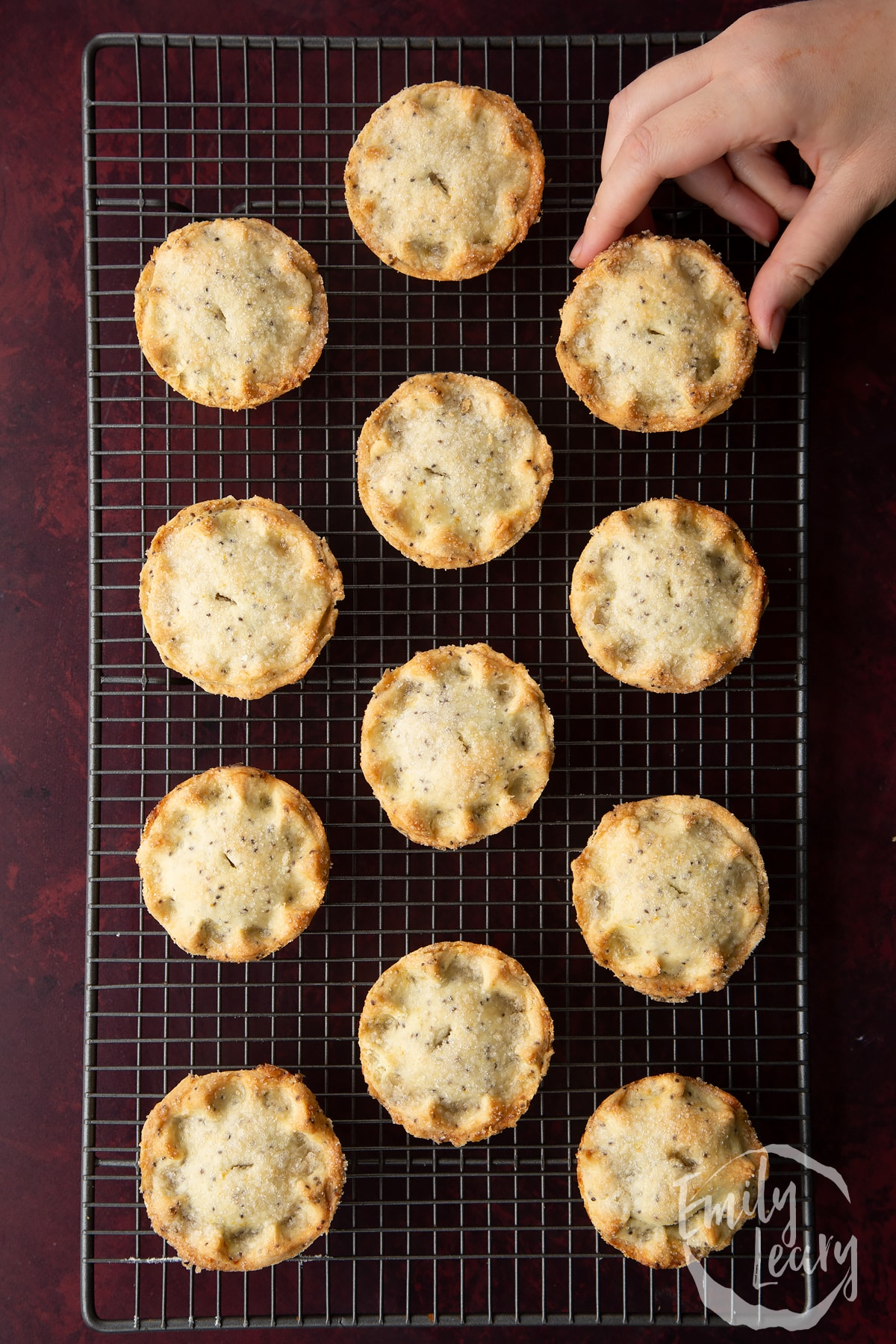 Freshly baked vegan mince pies on a wire cooling rack. A hand reaches for one.