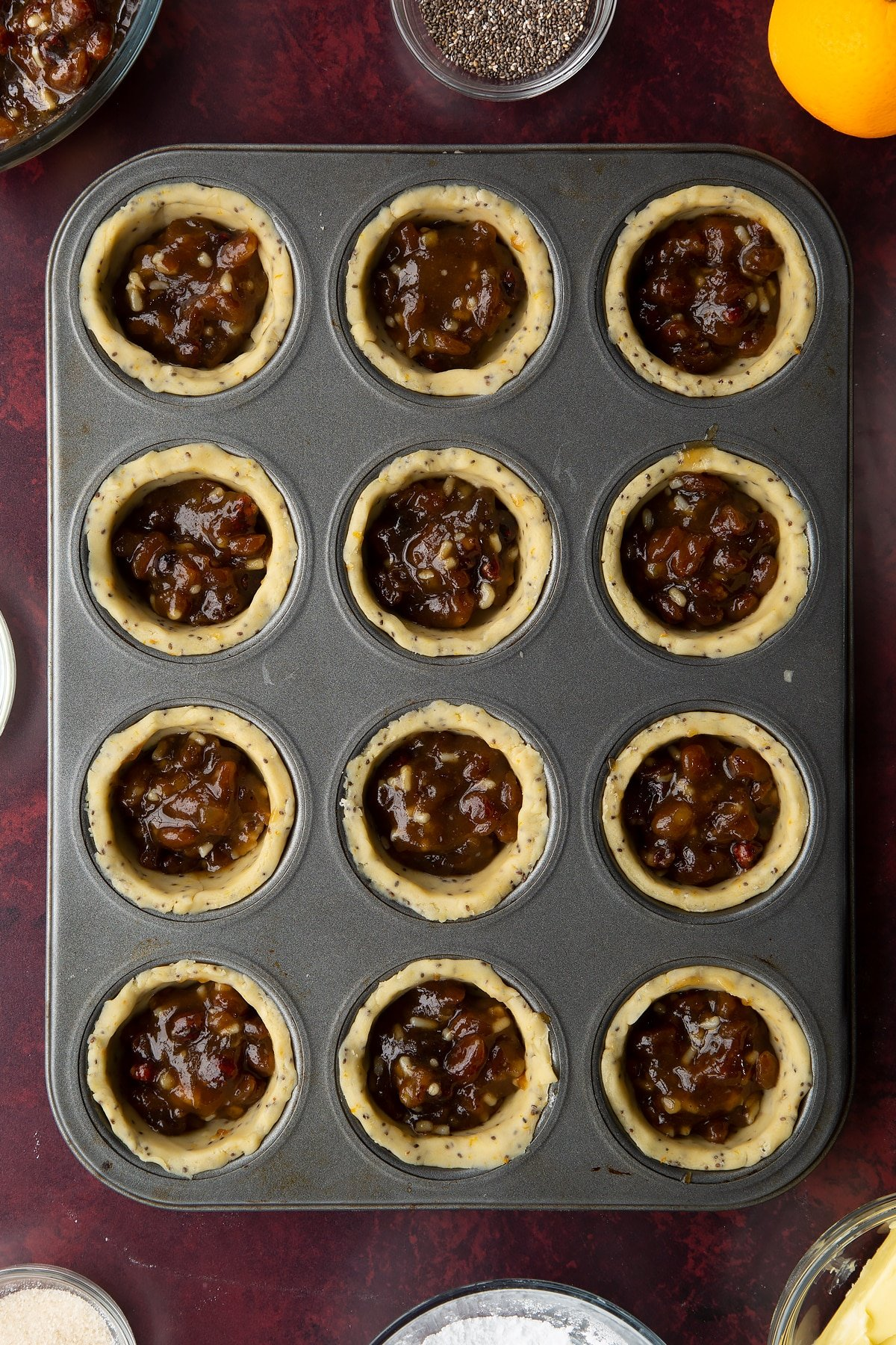 12-hole muffin tray lined with vegan pastry and filled with mincemeat.