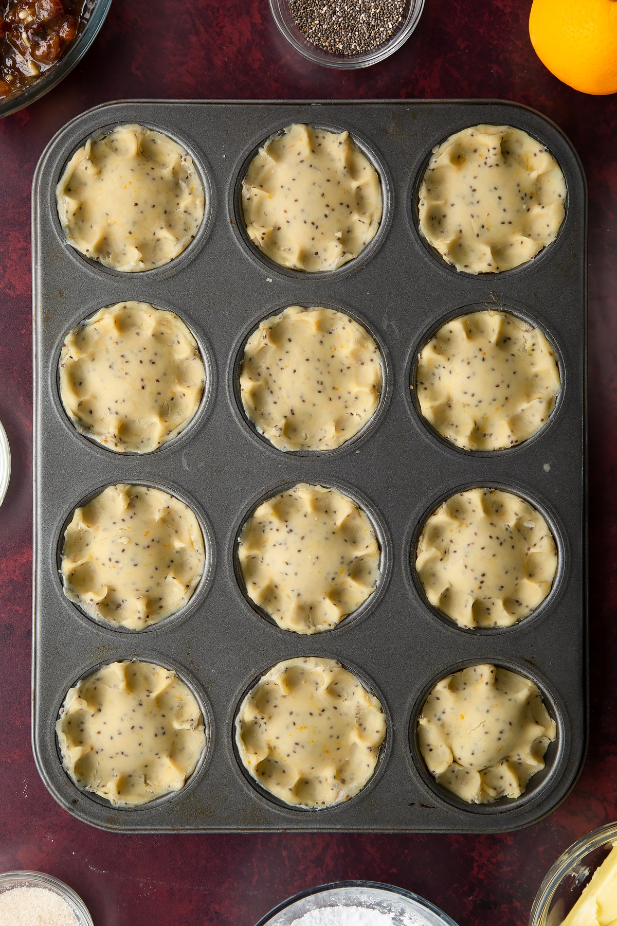 Uncooked vegan mince pies in a 12-hole muffin tray.