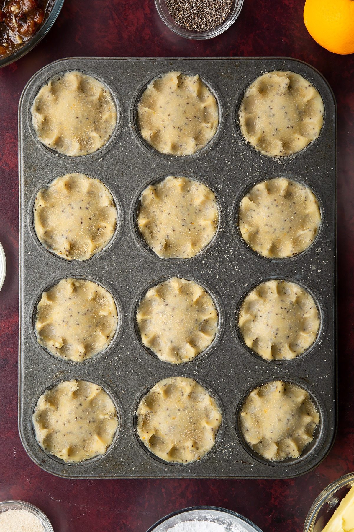 Uncooked vegan mince pies, brushed with milk and sprinkled with sugar in a 12-hole muffin tray.