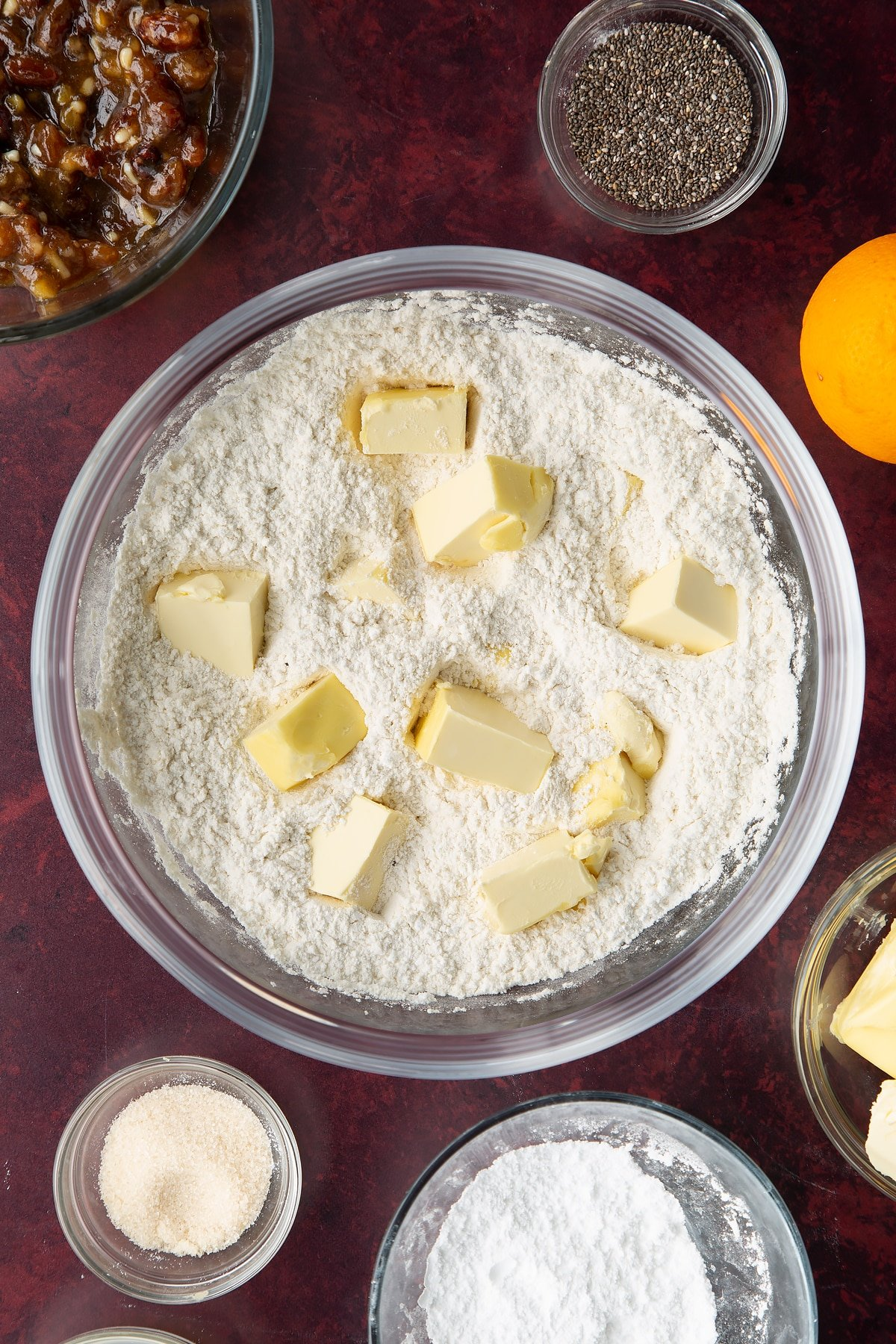 Flour and icing sugar mixed together in a bowl with cubes of vegan butter. Ingredients to make a vegan mince pie recipe surround the bowl.
