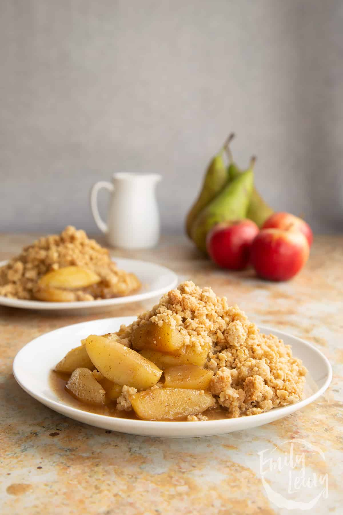 Apple pear crumble served to a small white plate.