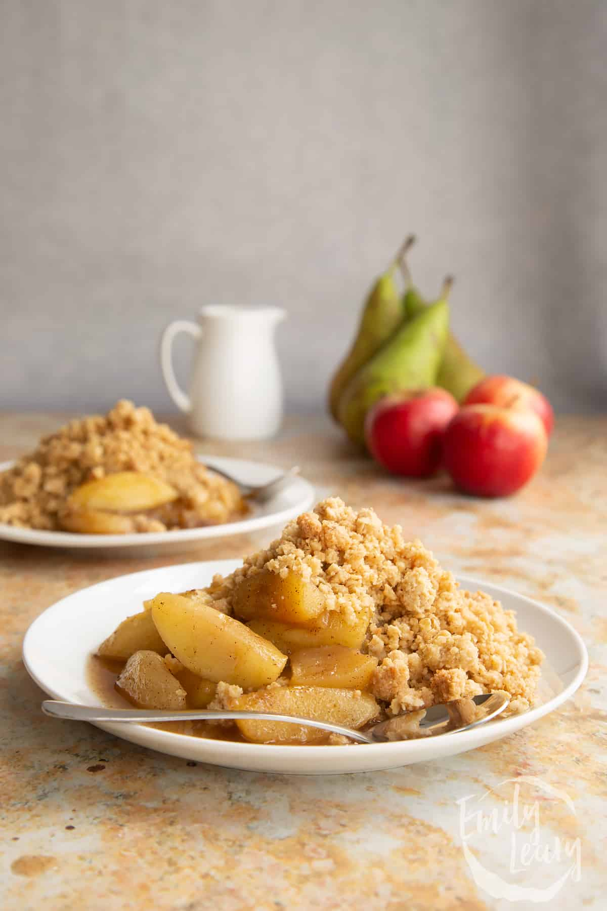 Apple pear crumble served to a small white plate with a small spoon.