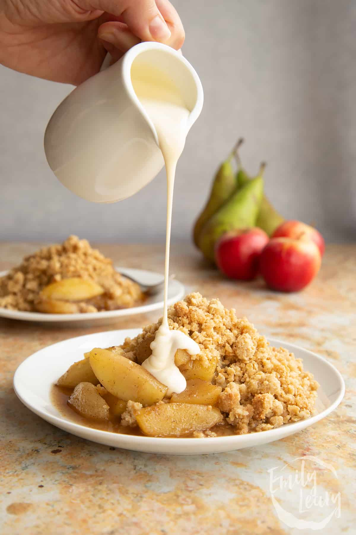 Apple pear crumble served to a small white plate. A hand pours a jug of custard above the plate.