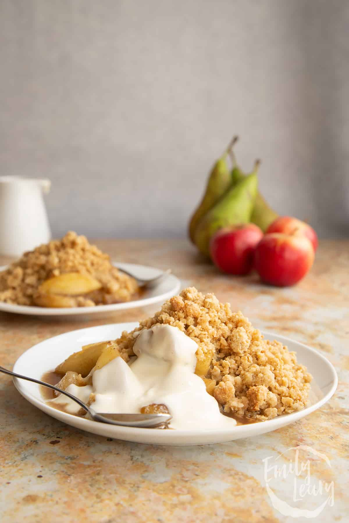 Apple pear crumble served to a small white plate with some custard and a small spoon.