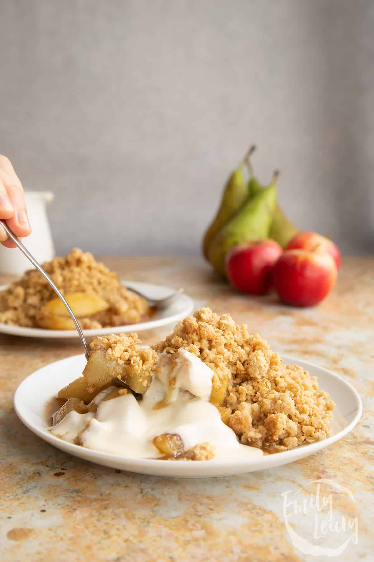Apple pear crumble and custard served to a small white plate. A hand holds a spoon delving into the crumble.