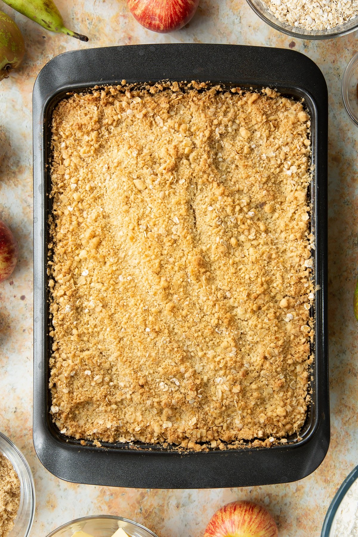 Freshly baked apple and pear crumble in a metal tray.