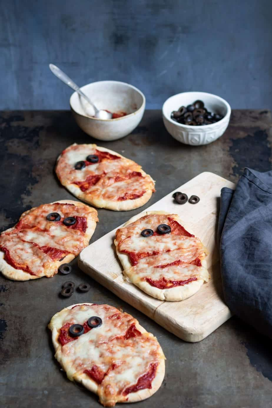 Mummy Halloween pizzas. The cheese gives the appearance of bandages and there are olives for eyes.
