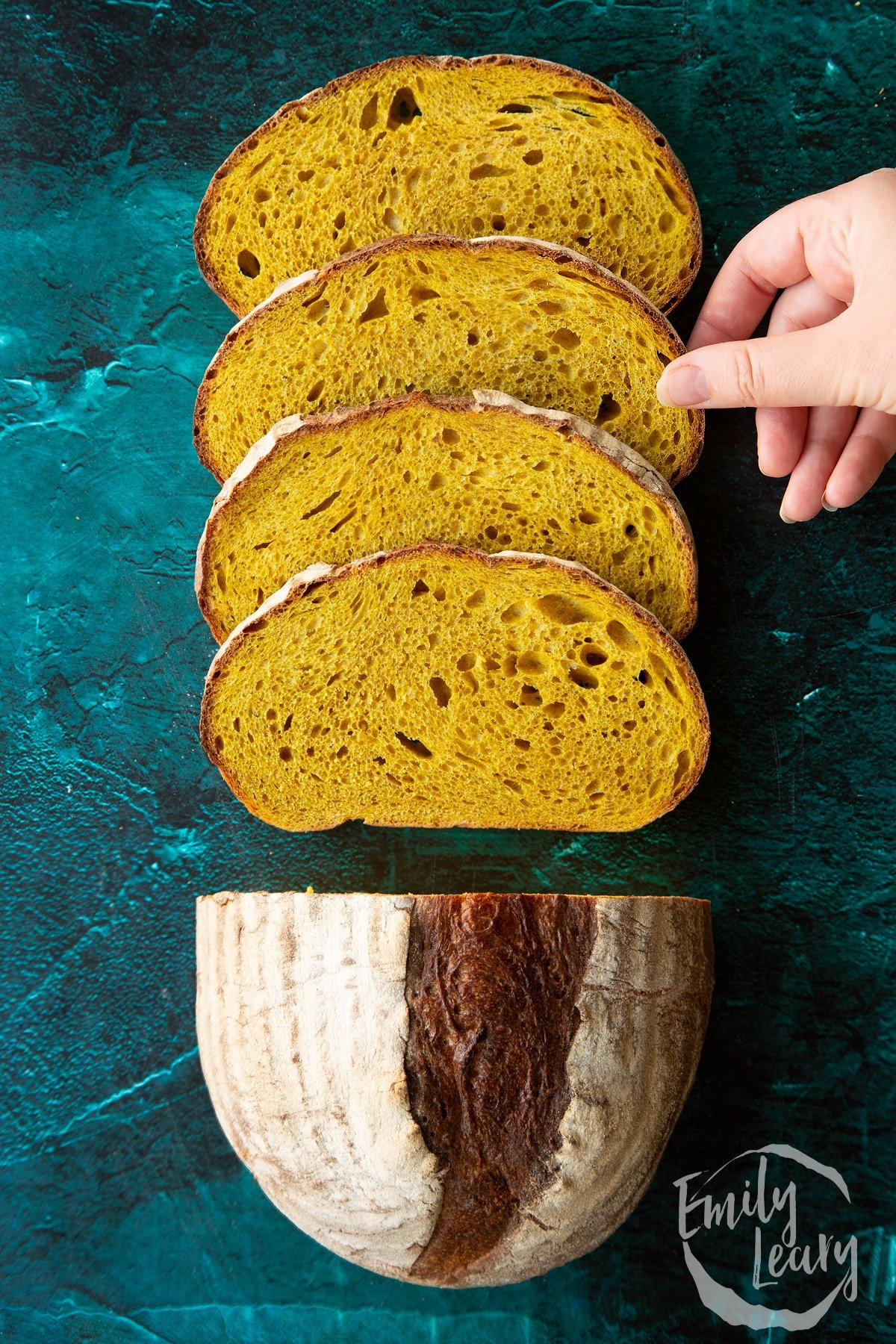 Pumpkin sourdough bread. Some has been cut into slices. A hand reaches to take a slice.
