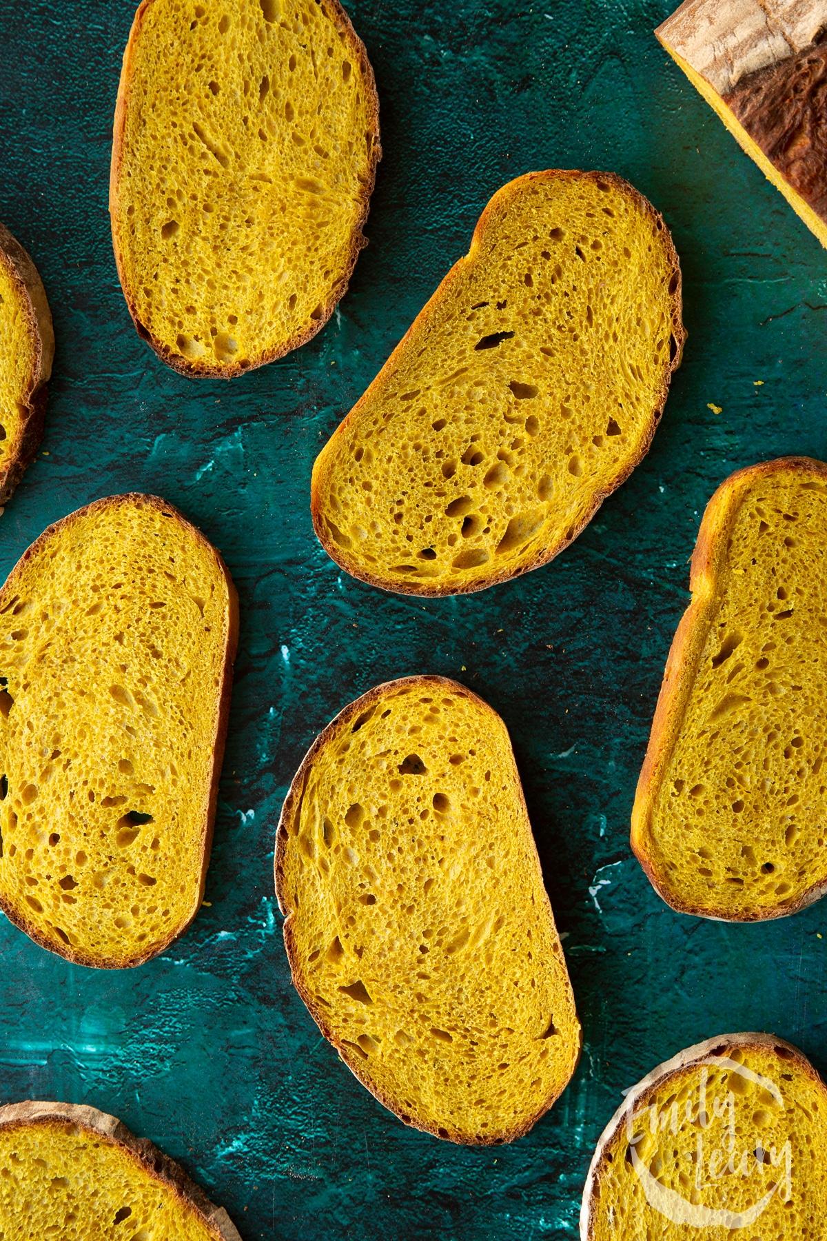 Slices of pumpkin sourdough bread arranged on a dark green surface.