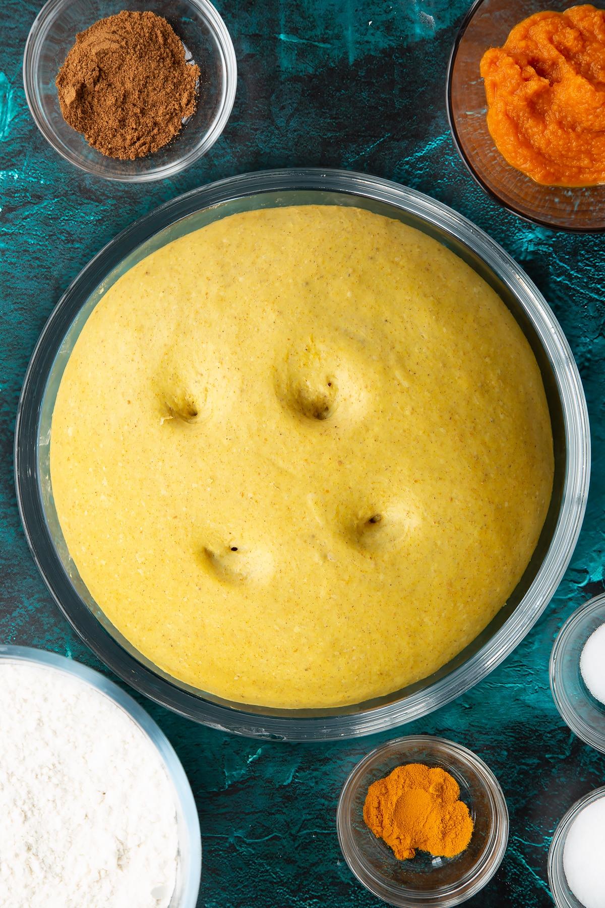 Risen pumpkin sourdough with four holes on top in a bowl. Ingredients to make pumpkin sourdough bread surround the bowl.