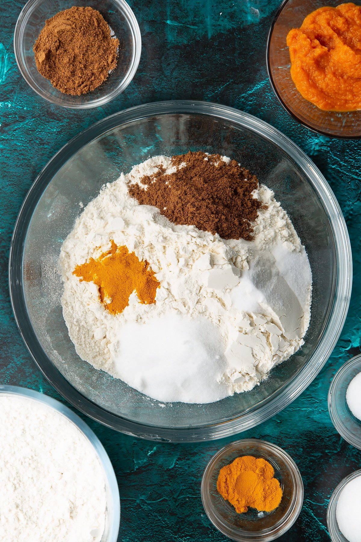 Flour, sugar, salt, mixed spice and turmeric in a bowl. Ingredients to make pumpkin sourdough bread surround the bowl.