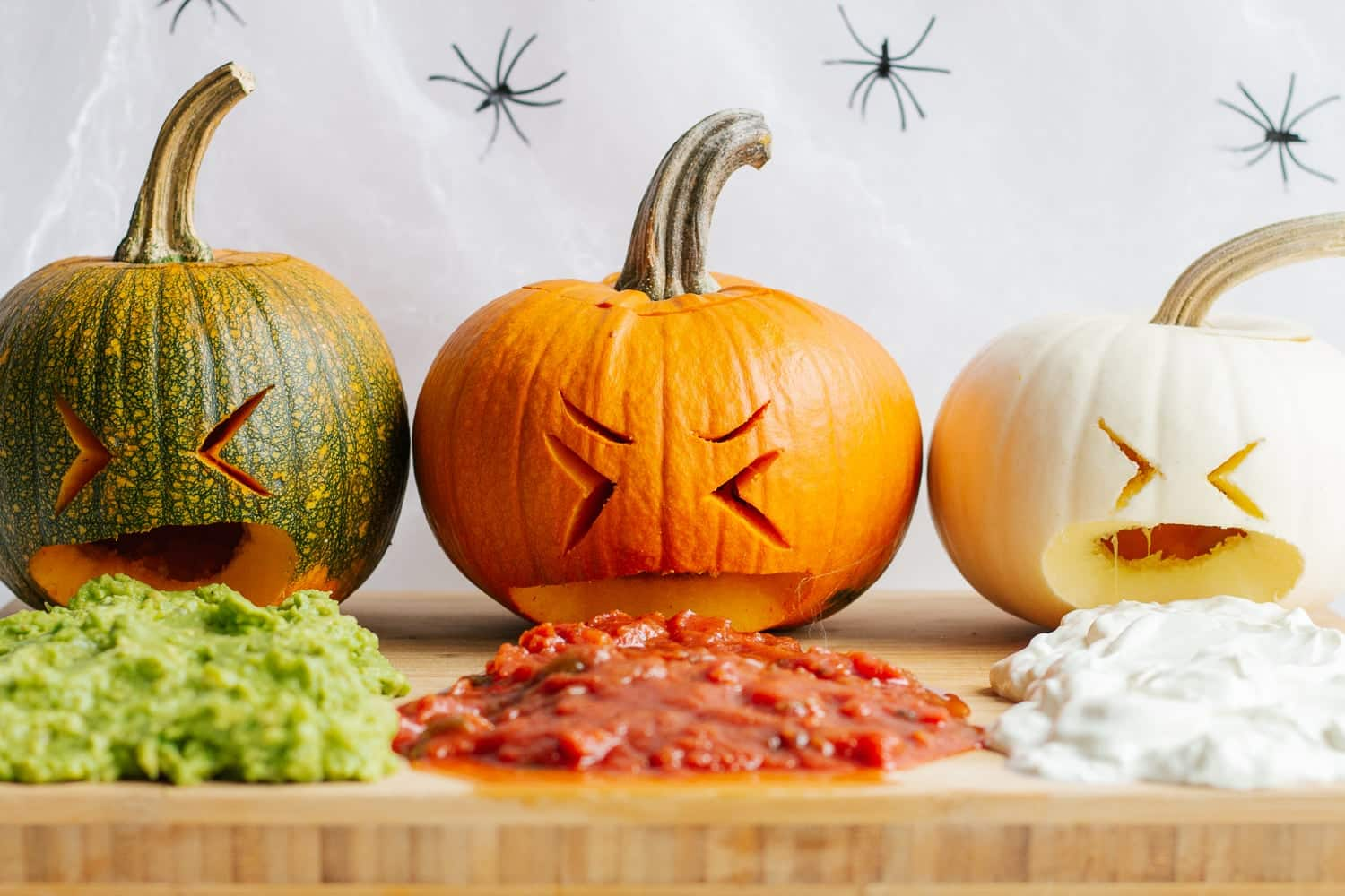 A row of three pumpkins. Each have cartoonish facial expressions and appear to be vomiting different taco sauces onto a board.