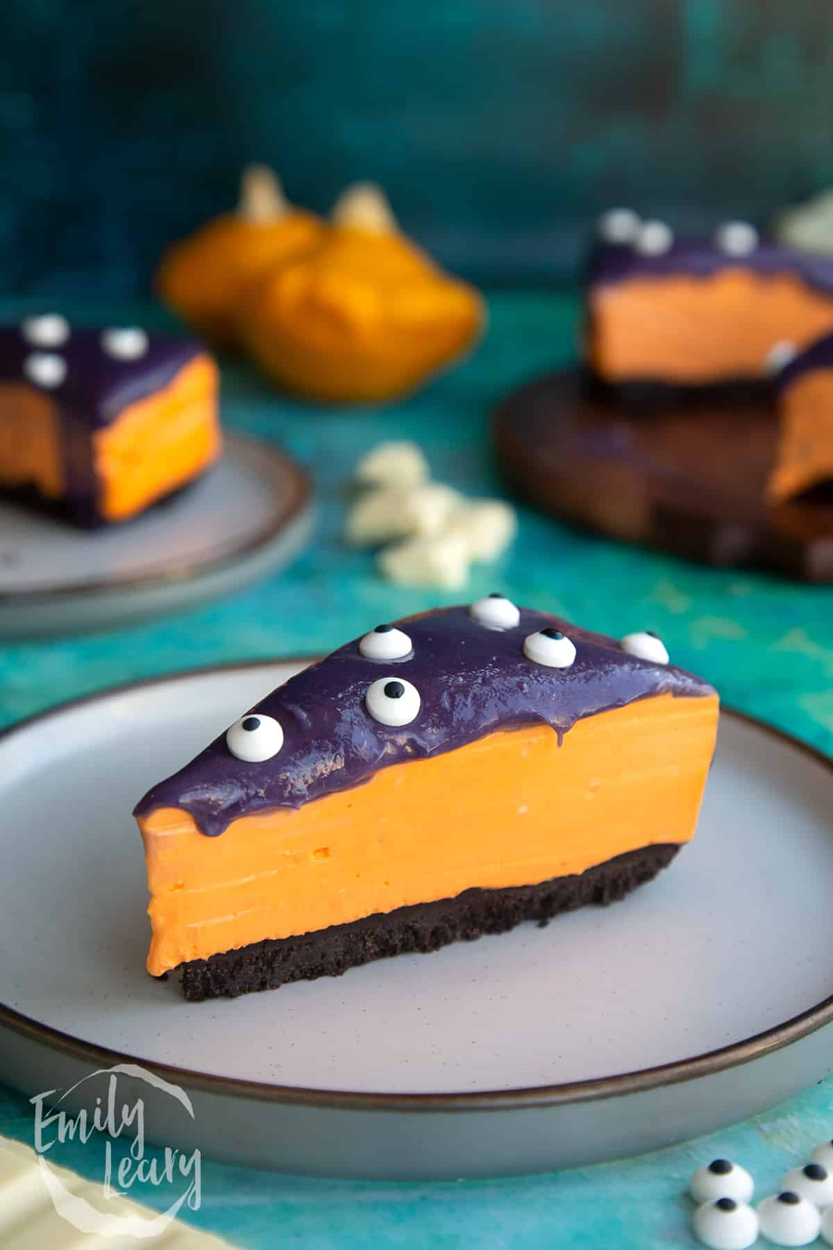 Slice of orange and strawberry Halloween cheesecake with an Oreo base on a plate.