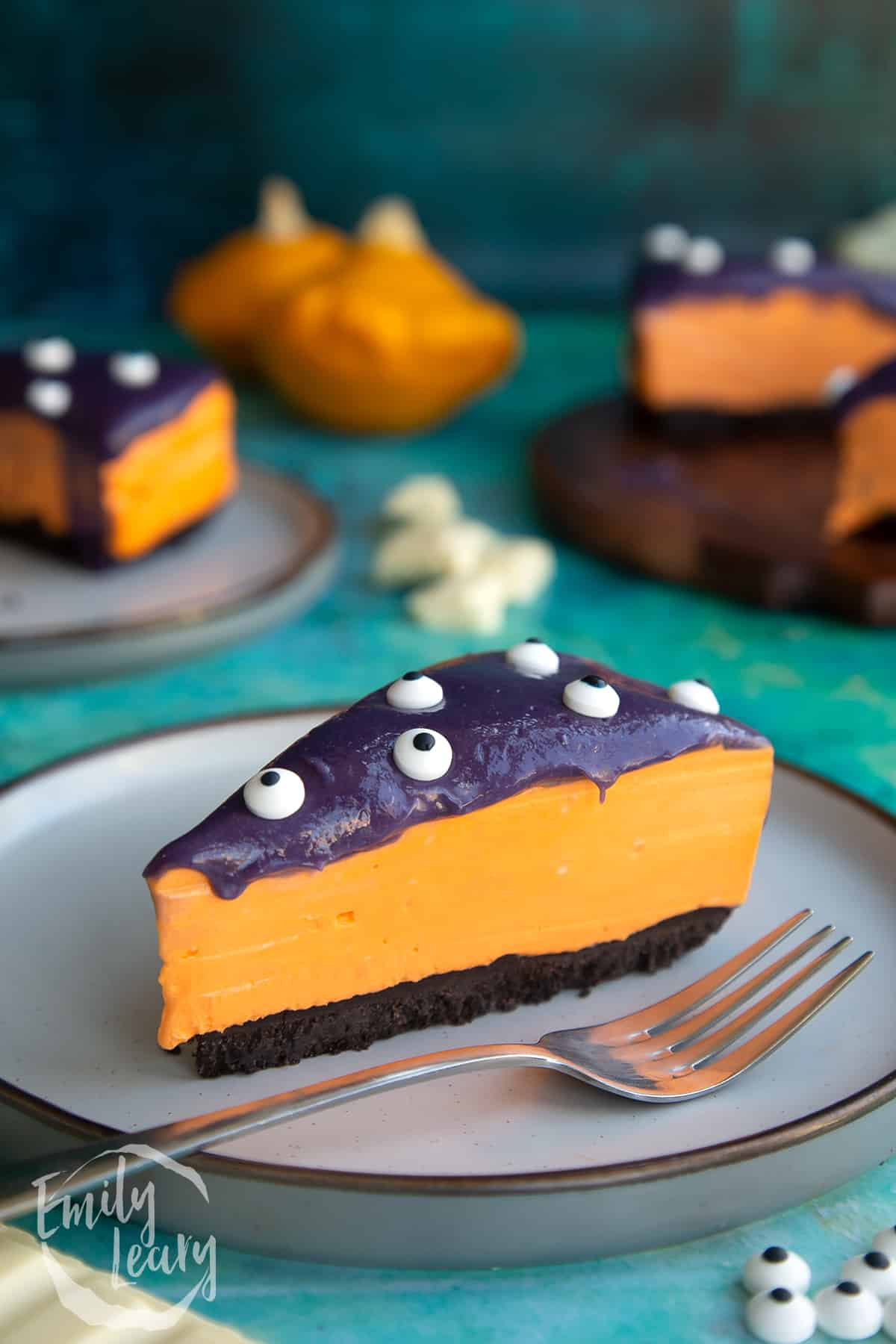 Slice of orange and strawberry Halloween cheesecake with an Oreo base on a plate with a fork.
