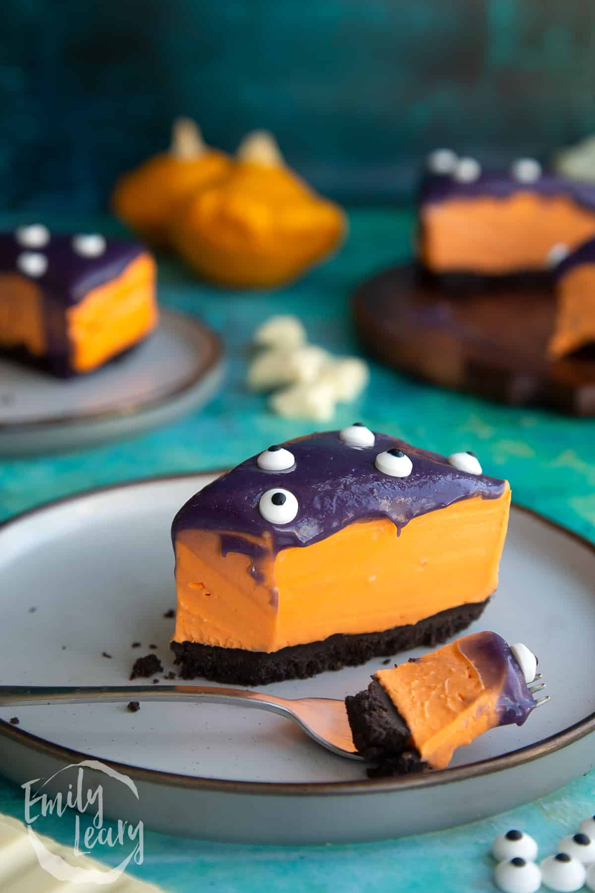 Slice of orange and strawberry Halloween cheesecake with an Oreo base on a plate. Some has been removed with a fork that rests on the plate.
