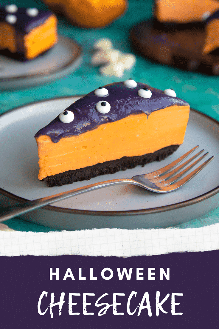 Slice of orange and strawberry Halloween cheesecake with an Oreo base on a plate with a fork. Caption reads: Halloween cheesecake.