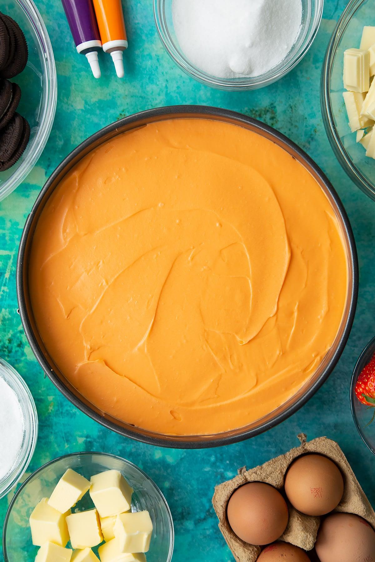 Orange cheesecake in a tin. Ingredients to make Halloween cheesecake surround the tin.