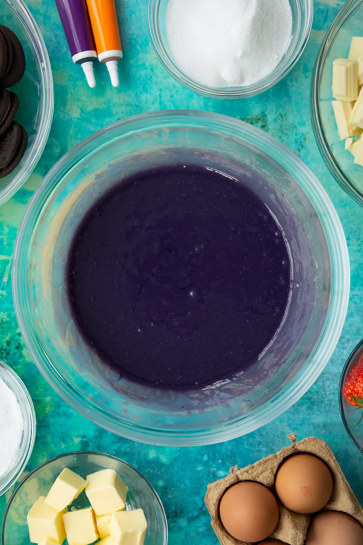 Purple dyed strawberry curd in a bowl. Ingredients to make Halloween cheesecake surround the bowl.