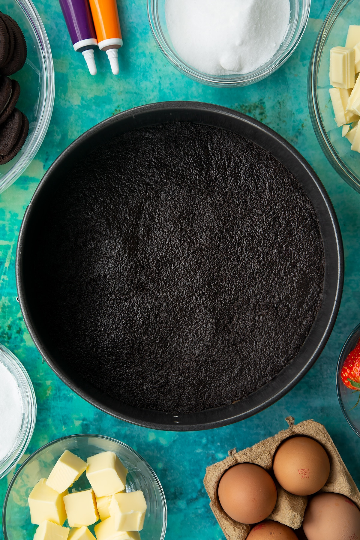 Oreo biscuit pressed into the base of a tin. Ingredients to make Halloween cheesecake surround the tin.