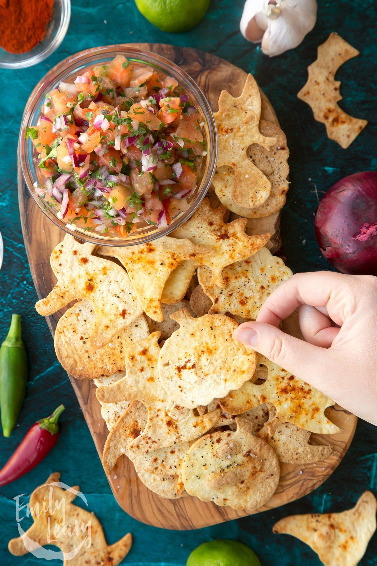 Halloween tortillas on a board with a small bowl of tomato salsa. A hand holds a pumpkin shaped chip.