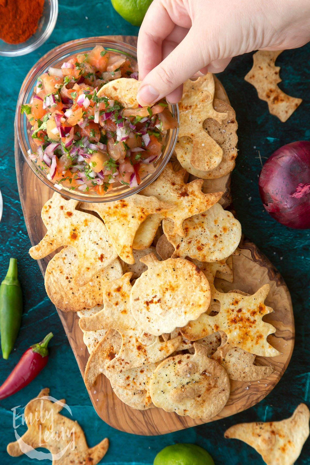 Halloween tortillas on a board with a small bowl of tomato salsa. A hand dips half a pumpkin shaped chip.