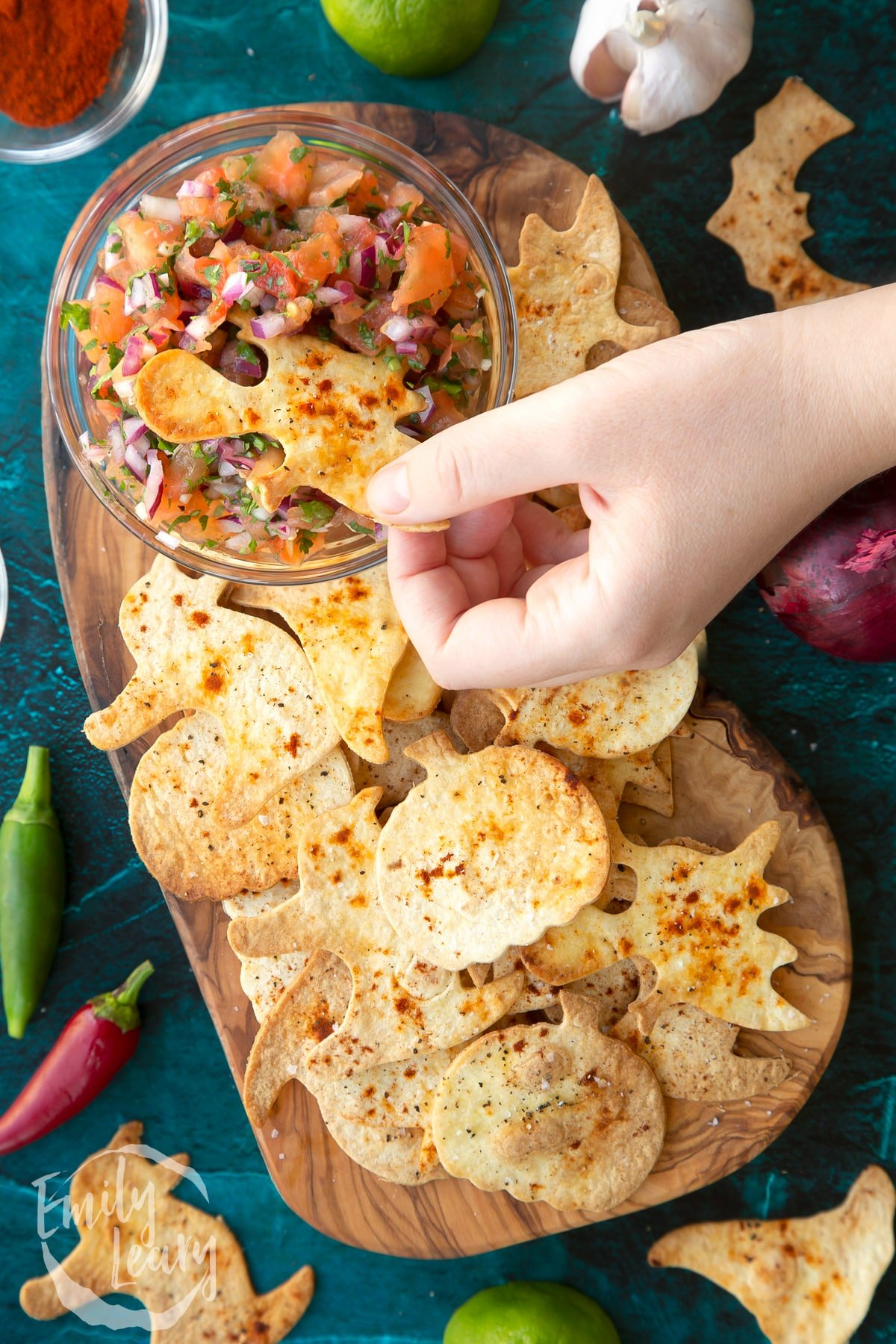 Halloween tortillas on a board with a small bowl of tomato salsa. A hand dips a ghost shaped chip.