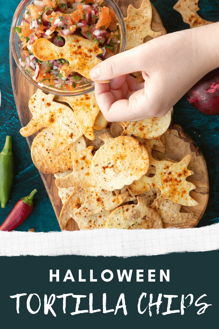 Halloween tortillas on a board with a small bowl of tomato salsa. A hand dips a ghost shaped chip. Caption: Halloween tortilla chips.