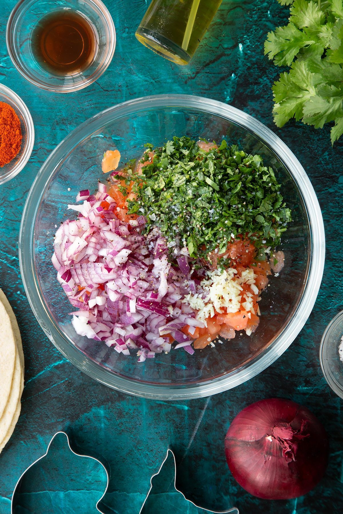 Chopped tomatoes, red onion, coriander, garlic, red wine vinegar and lime juice in a glass bowl
