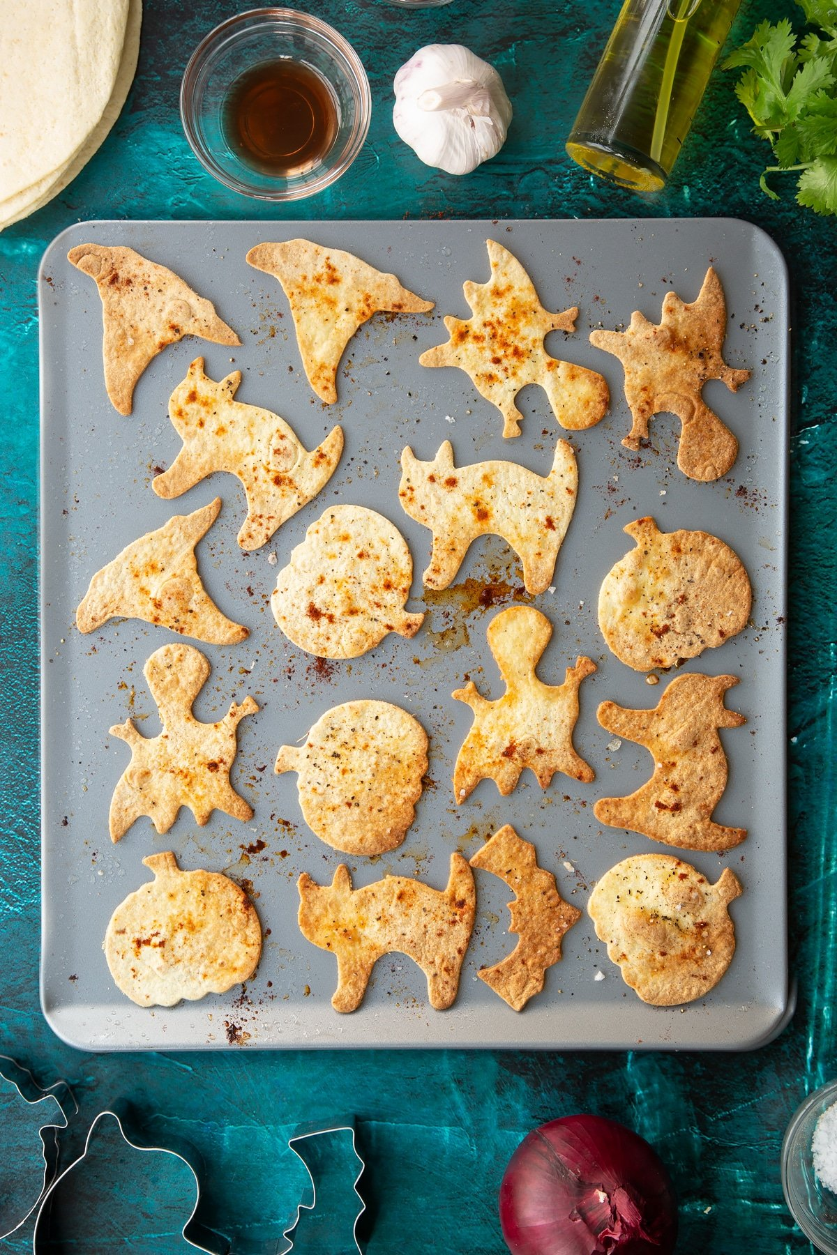 Baked Halloween tortillas on a baking tray, sprinkled with salt, pepper and paprika.