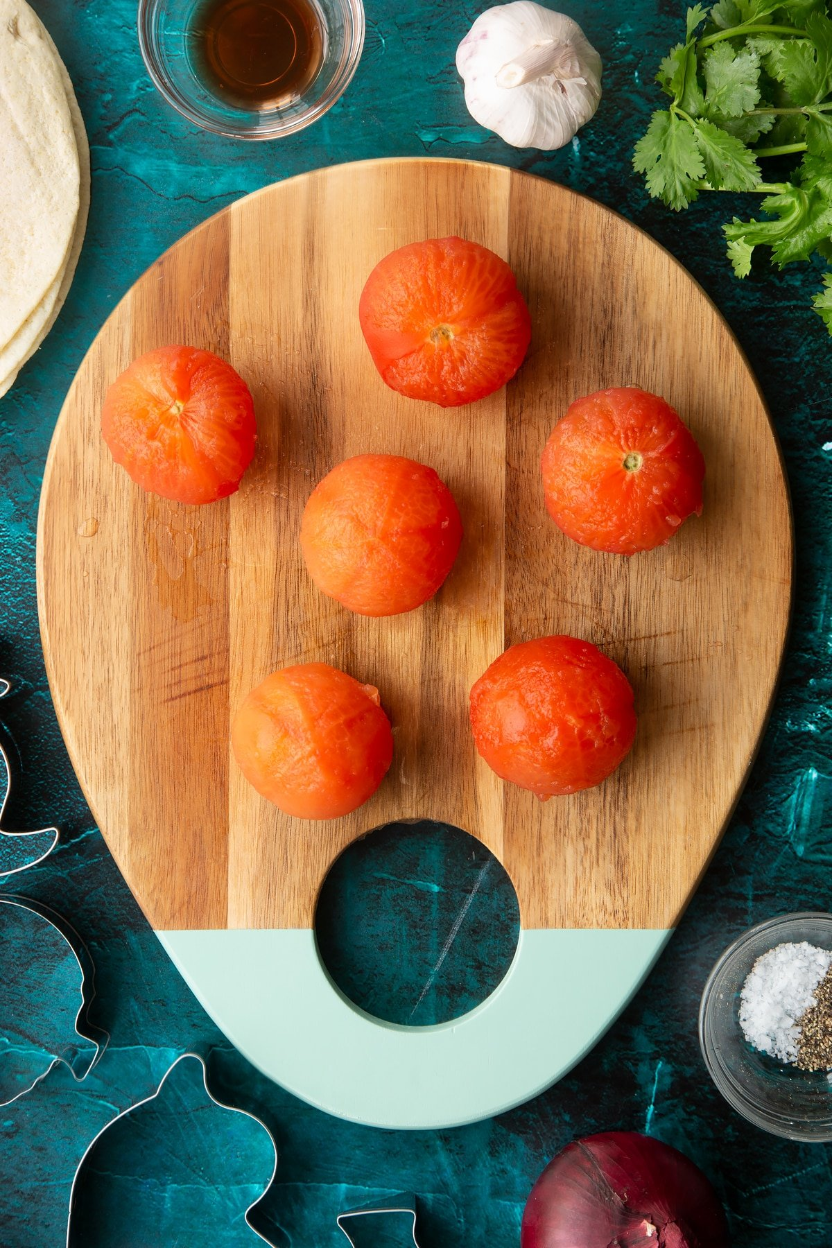 Peeled tomatoes on a wooden board.
