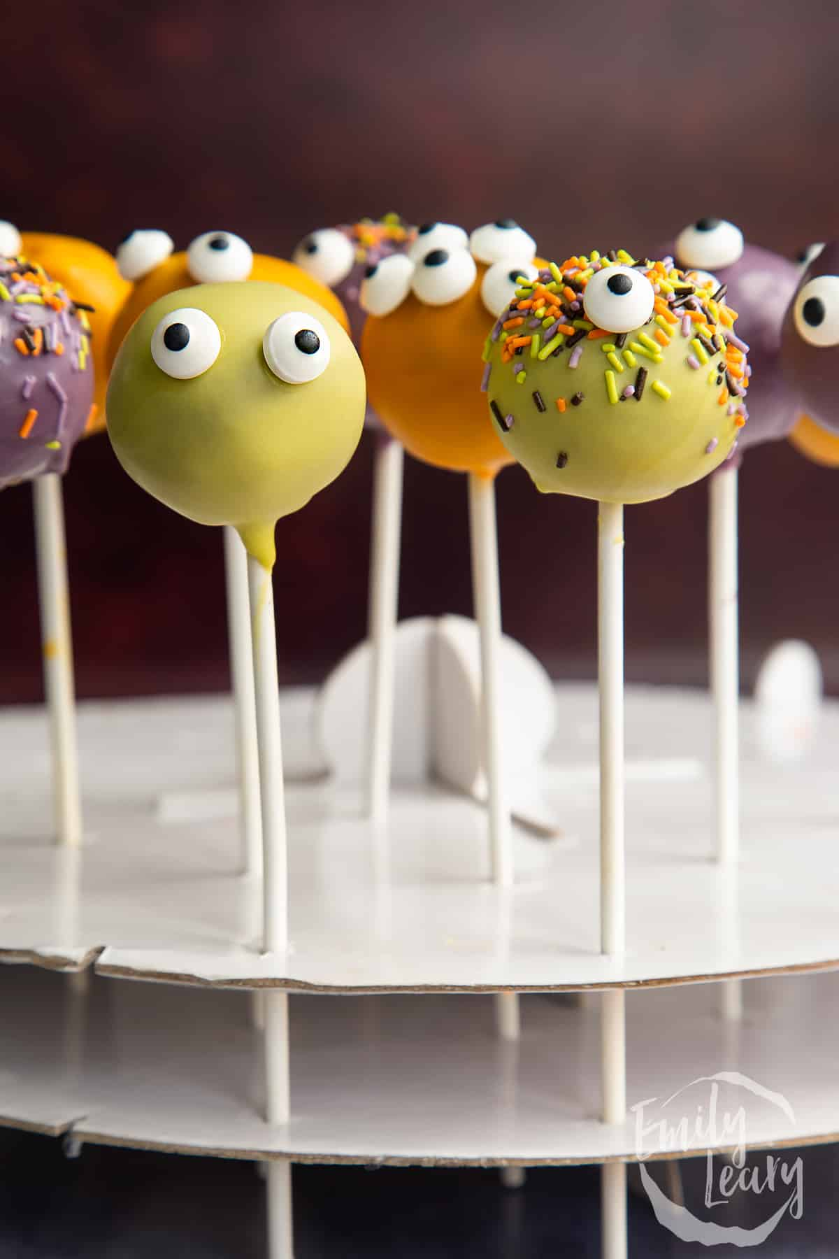Halloween cake pops standing in a white cardboard cake pop stand.