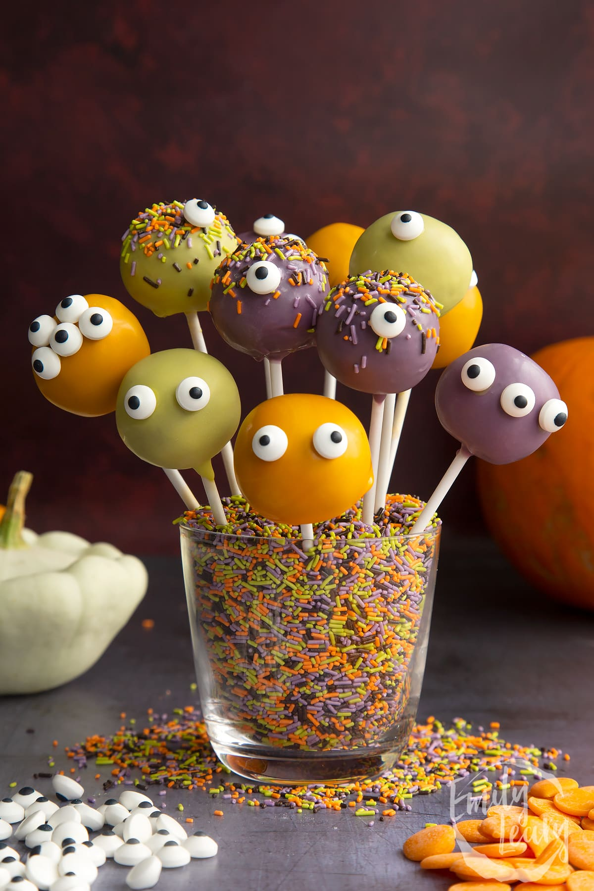 Halloween cake pops standing in a glass filled with Halloween sprinkles.