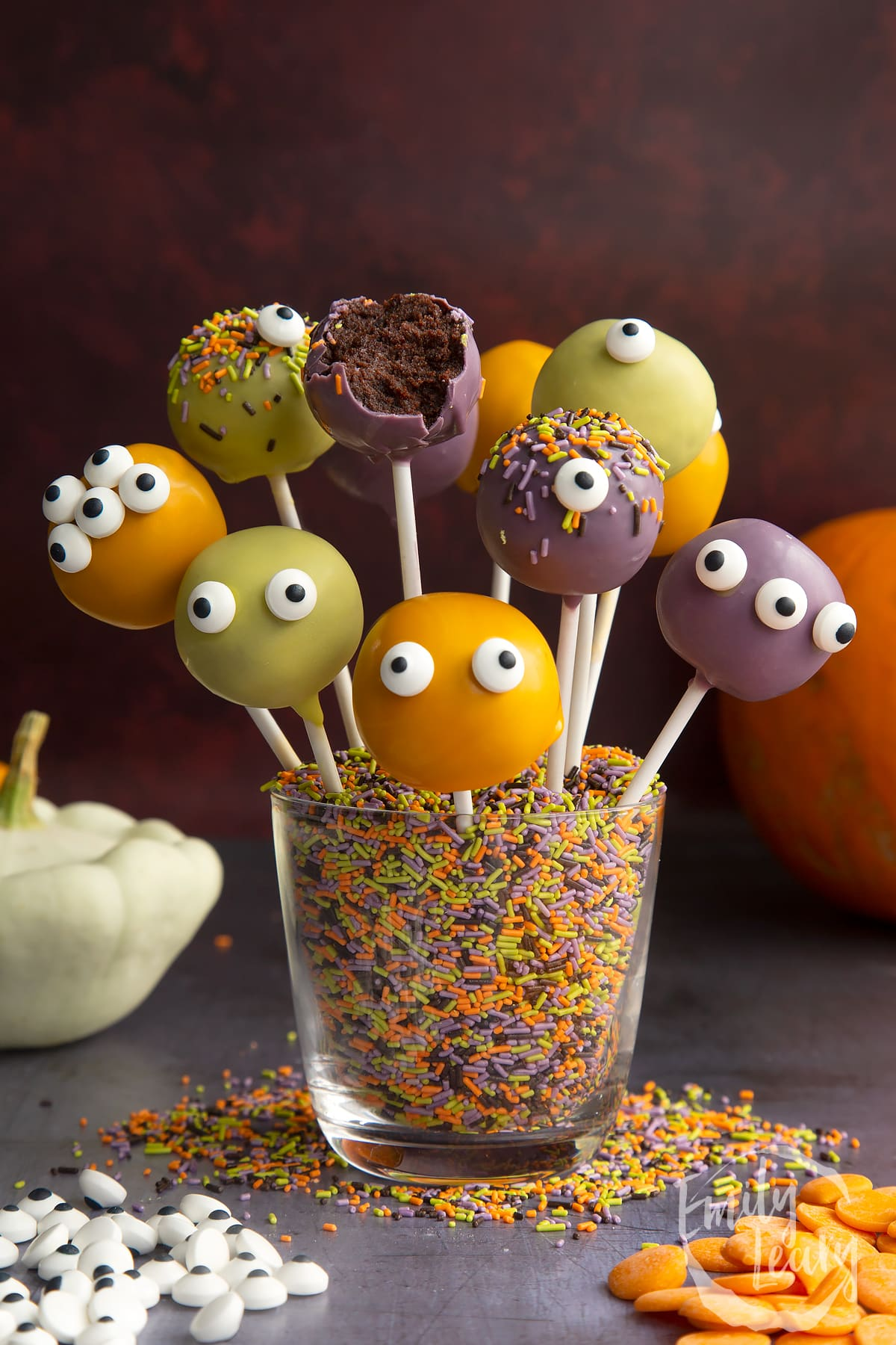 Halloween cake pops standing in a glass filled with Halloween sprinkles. One has been bitten open.