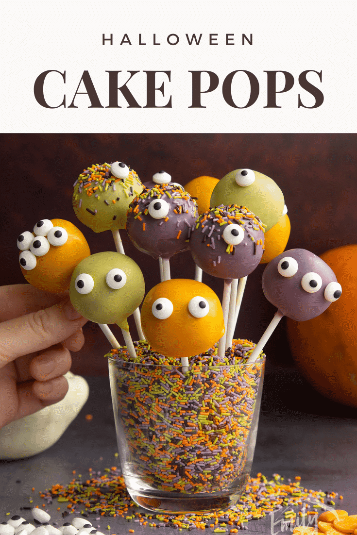 Halloween cake pops standing in a glass filled with Halloween sprinkles. A hand reaches for one. Caption reads: Halloween cake pops.